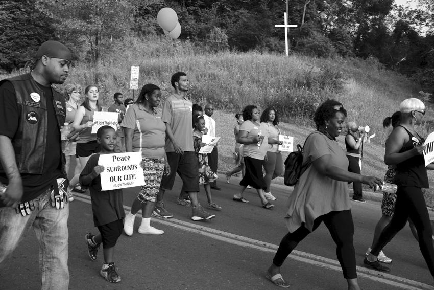 Marching past makeshift white crucifix on E. Fayette Street. Michael Davis Photo   Syracuse New Times